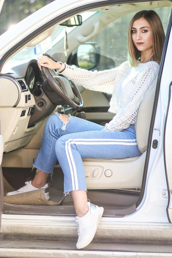 Young girl in the luxury car. Pretty young girl in a casual clothes sitting in the modern luxury off-road car stock photography
